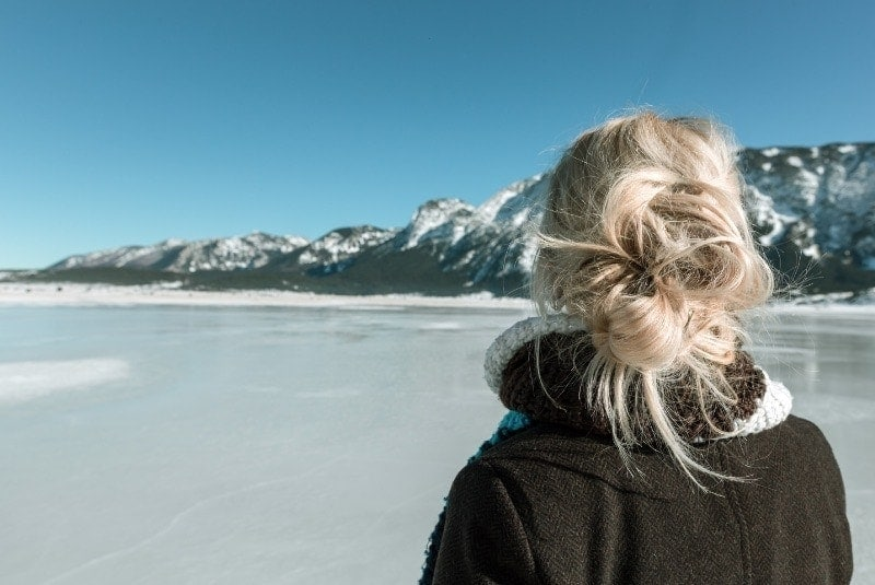 Lady looking at a frozen lake and a mountain to get ready for ice skating marathon